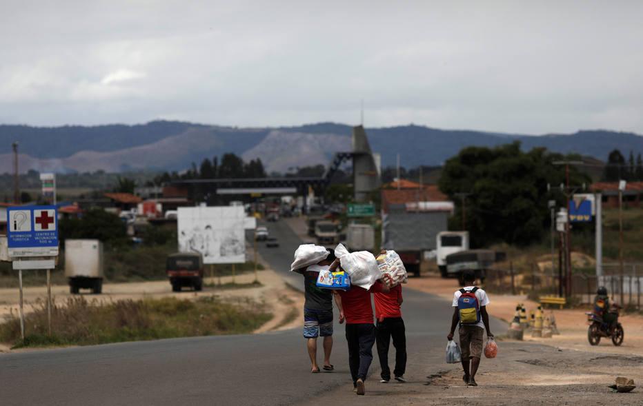 Venezuelanos voltam ao seu país depois de comprar comida na cidade de Pacaraima, em Roraima, no Brasil, antes do fechamento da fronteira. Crédito:  Ricardo Moraes/Reuters