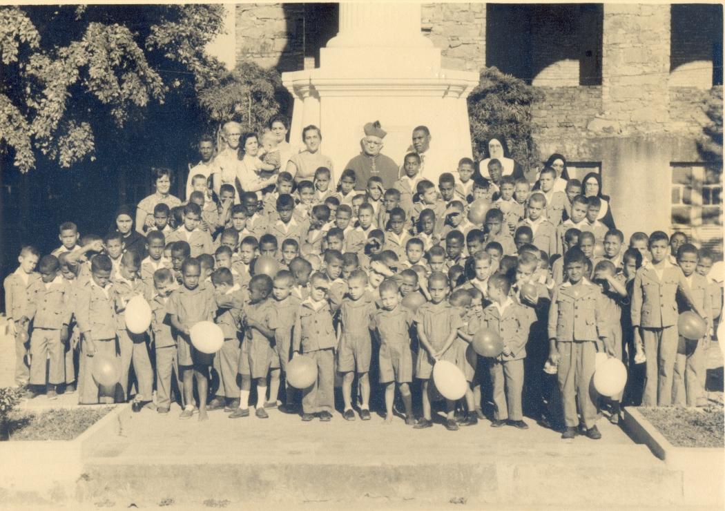 Crianças do Orfanato Cristo Rei com o Arcebispo Dom João Batista da Mota e Albuquerque (ao centro) e Irmã Marcelina de São Luiz (última à direita). Crédito: Acervo do Arquivo Público Estadual