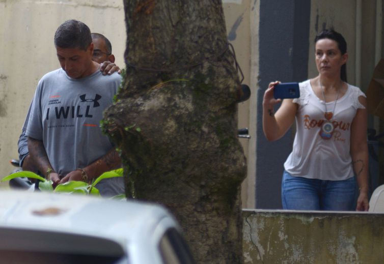 Ronnie Lessa, suspeito do assassinato da vereadora Marielle Franco, é escoltada por um policial quando ele deixa o departamento de homicídios para prestar depoimento na justiça Rio de Janeiro.