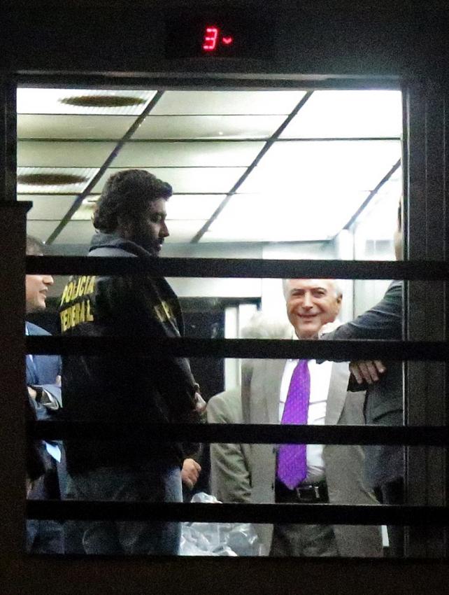 O ex-presidente da República Michel Temer (de gravata roxa), deixou a superintendência da Polícia Federal, no centro do Rio, no início da noite de segunda-feira (25). Crédito: FABIO MOTTA/Estadão