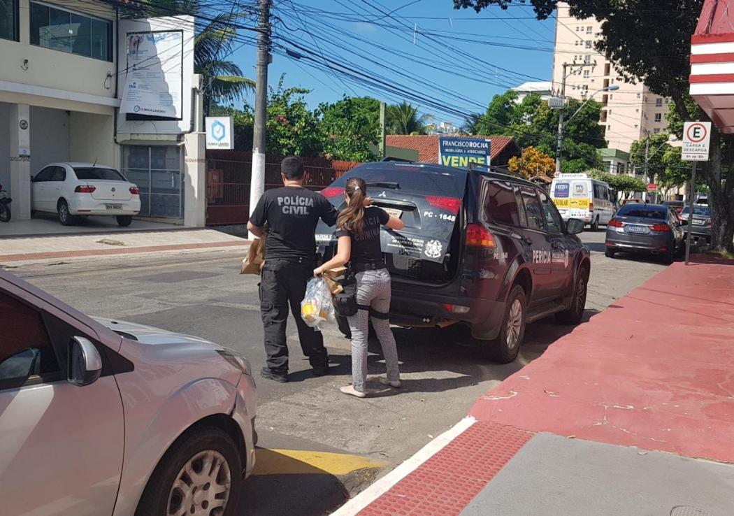 Peritos da Polícia Civil com sacola contendo brinquedos. Crédito: Patricia Scalzer