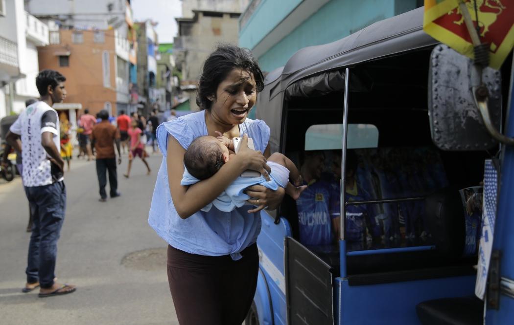 Populares que moram perto do Santuário de Santo Antônio, em Colombo, no Sri Lanka, correm a procura de um lugar seguro depois que a polícia encontrou explosivos em veículos estacionados na região, nesta segunda- feira, 22. Crédito: Eranga Jayawardena