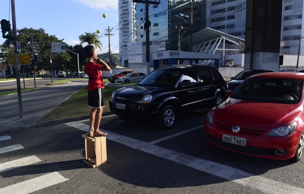 Menino de 14 anos fazendo malabarismo em um semáforo das ruas de Vitória para ganhar dinheiro. Crédito: Ricardo Medeiros