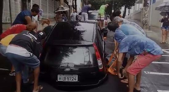 Grupo de pessoas tiram um carro de uma cratera. Crédito: Reprodução/Gazeta Online