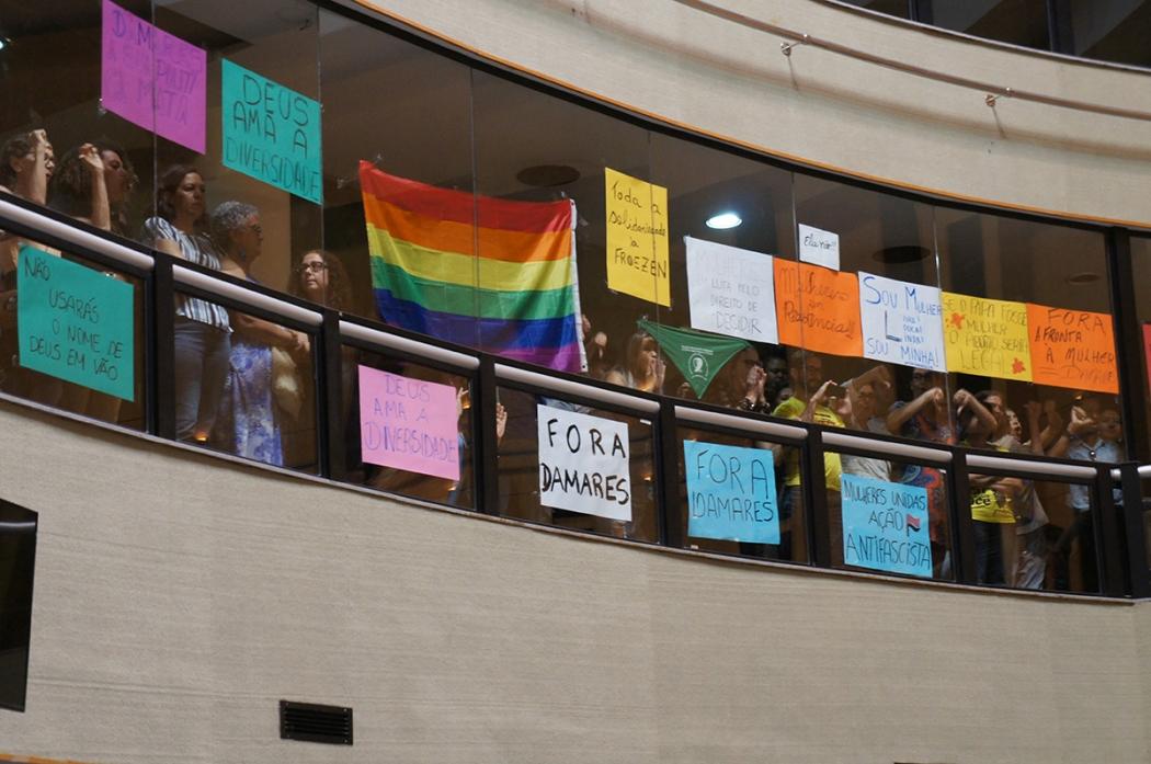 Cartazes e manifestantes na galeria da Assembleia Legislativa em protesto contra a ministra Damares Alves. Crédito: Lissa de Paula/Ales