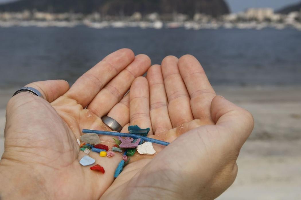 O biólogo Jonas Leite, doutor em oceanografia, presidente do Instituto Meros do Brasil, mostra microplástico vindo do mar coletado na areia da praia de Botafogo. Crédito: Fernando Frazão/Agência Brasil