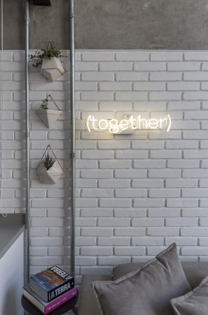 O loft com estilo industrial e base clara, assinado pela arquiteta Carina Korman, do escritório Korman Arquitetos, ganhou plantinhas com vasinhos bem modernos e, ao lado, um letreiro de neon. Um toque sutil para combinar com a nova estação. Crédito: joao paulo s.de oliveira