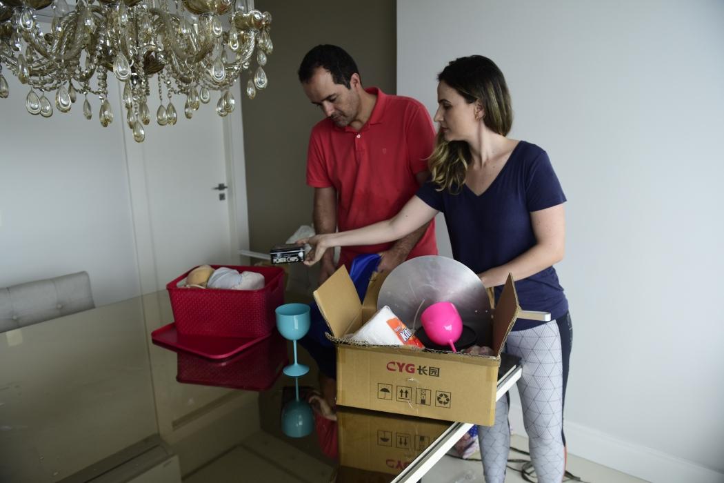 Elieser e a esposa Fernanda retiram os objetos das caixas para arrumarem o apartamento. Crédito: Ricardo Medeiros