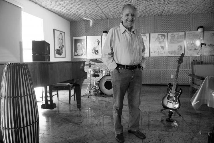 O empresário, escritor e músico Cariê Lindenberg posa na sala de música de sua casa, na Ilha do Frade, em Vitória. Crédito: Mônica Zorzanelli